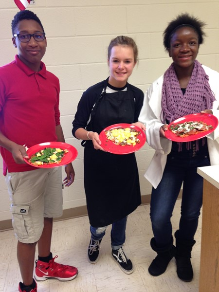 Students proudly display the meal that they made during their food lab class.
